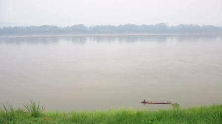 A fisherman in a wooden rowboat is going out to the Mekhong river in the morning. (HD footage with sound) Stock Footage