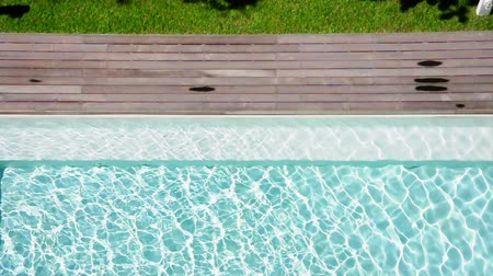 Shiny blue water in a swimming pool and wooden pathway. (HD footage with sound) Stock Footage