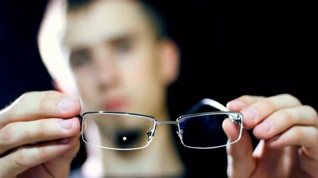 livro : A man checking its eyesight glasses. Very careful not to destroy the glass and framework of glasses, there is already a bit of error on the glasses. HD1080p.