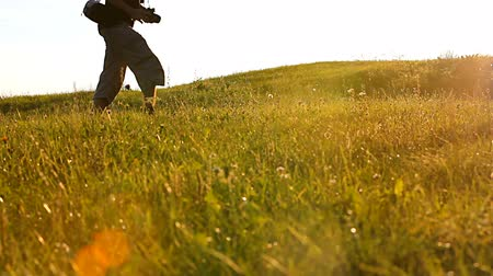 fényképész : Photographer hikingwalking in a sunset over lawn. EOS 550D. 1080p. Tripod. Stock mozgókép