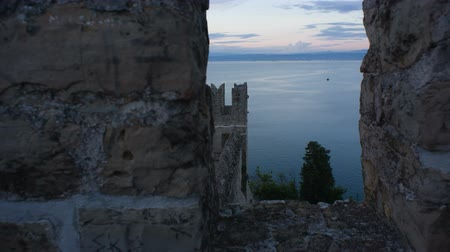 zamek : Shot of sea landscape with castle wall in front from behind the wall with window. Shot in slider. Prores 422 10bit
