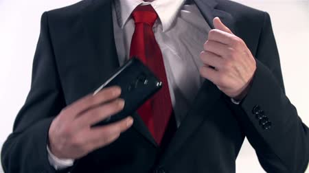 people talking : Man In Suit Placing Mobile Phone in Inside Pocket