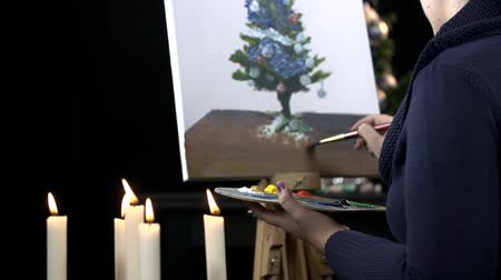 basit : Artist drawing Christmas with candles in front