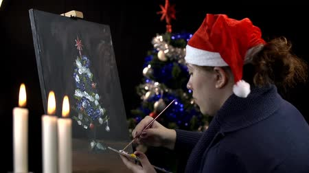 рождественская елка : Young woman mixing color on palette and drawing Christmas tree Стоковые видеозаписи