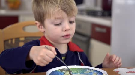 galuska : Close up of young boy eating soup with noodles