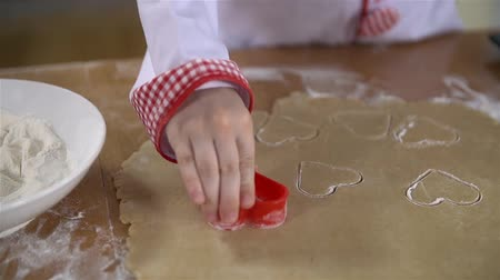 keksz : Little cook stamping hearts in dough fort cookies Stock mozgókép
