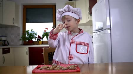 keksz : Little cook making cute face after biting cookie