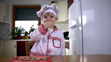 Child in cook outfit trying out cookie