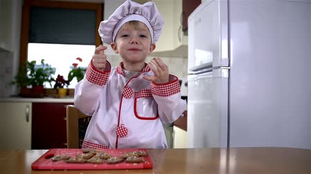 keksz : Very young baker in kitchen enjoying eating cookie