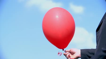 rests : Man Lets Go Red Balloon In To The Blue Sky Stock Footage