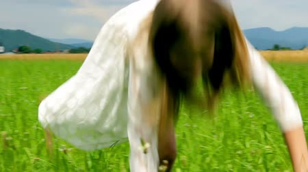 jump : Close Up Girl in White Dress Making Wheel on Grass Stock Footage