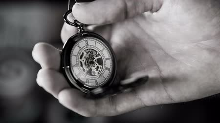 clock hands : Setting Time on Pocket Watch Slow Motion Black and White. Small pocket clock in man hands close up.