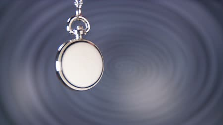 hipnoza : Spinning Small Pocket Watch. Classic pocket clock spinning in front of hypnosis background spiral.