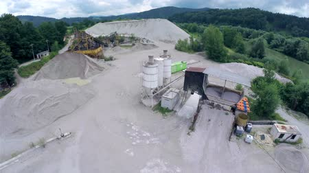 macadam : Aerial flight over sand machinery. Flight over piles of sand in bad weather.
