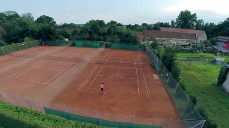 tennis game : Aerial flight over tennis court with person playing alone