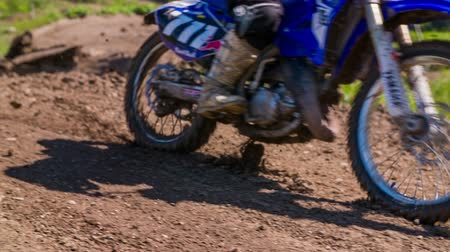 toprak : Motocross bike landing on dirt close up in slow motion. Landing of motorbike on motocross dirt track, close up on tires undermine mud on land. Stok Video