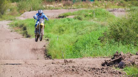 lovas : Long shot of motocross racer flying after jump in slow motion. Rider jumping in to air after speeding on motocross track.