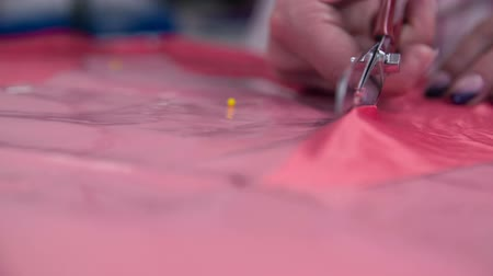 makas : Scissors cutting textile front shot slow motion close up. Tailor cutting pieces from blank textile for new elegant dress with measured plastic foils.