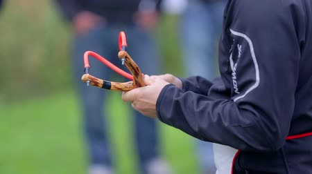 tiro : Person prepares for slingshot shooting. Close up of male hands putting projectile in to slingshot holder and fires. Stock Footage