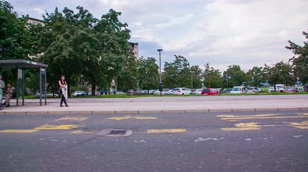 otobüs : LJUBLJANA, SLOVENIA ? SEPTEMBER 2014: Bus stop driving by with trees and cars in background. People waiting on bus stop, driving by in slow motion. Stok Video