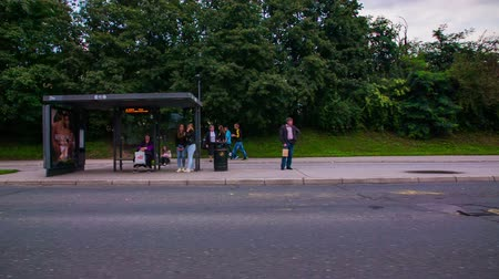 bekleme : LJUBLJANA, SLOVENIA ? SEPTEMBER 2014: Bus stop people waiting for ride slow motion passing by. Driving by a bus stop in slow motion people standing and waiting.
