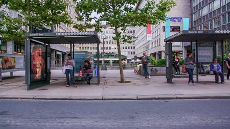 bekleme : LJUBLJANA, SLOVENIA ? SEPTEMBER 2014: Driving by a bus stop with many terminals and people waiting. Bavarian Palace bus stop in Slovenia from cars perspective in slow motion. Stok Video
