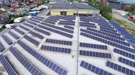 building heat : Solar panels on big storage building aerial footage. Flat building with lines of solar power station producing electricity for industry aerial flight over.