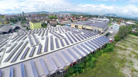 панель : Flying closer to small business buildings with solar panels on roof. Flat building with lines of solar power station producing electricity for industry aerial flight over. Стоковые видеозаписи
