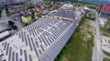 устанавливать : Industrial complex with solar panels on roof aerial footage. Flat building with lines of solar power station producing electricity for industry aerial flight over.