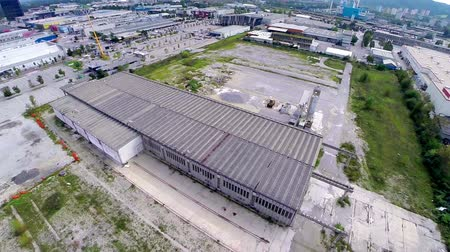 çatılar : Flying around storage industry house. Wide air shot of flat building with overgrown grass around.