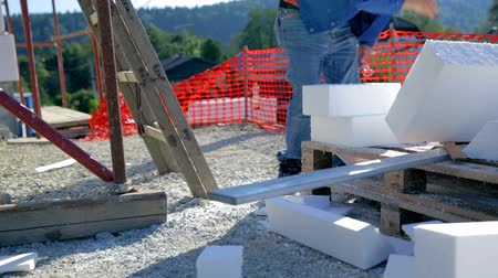 acabamento : Sawing foam and checking measures. Construction worker preparing measured board of foam. Stock Footage