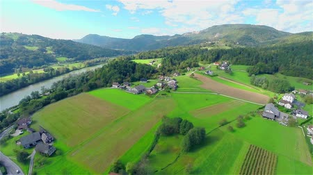 slovinsko : Panning around a village and nature landscape aerial footage. Flying high above small villages, panning around on a sunny day with a lot of green landscape.
