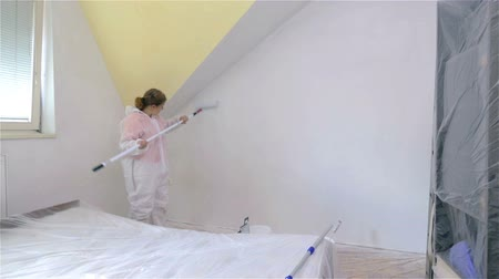 malarstwo : Painting old room. Woman with long stick with roller on the end painting tall wall. Wideo