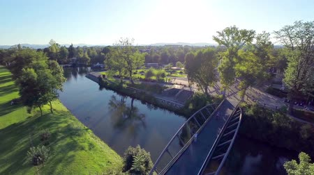 small park : Flying over small bridge on Ljubljanica river at sunset. Wide aerial footage of park with bridge over Ljubljanica river at sunset and people walking over.