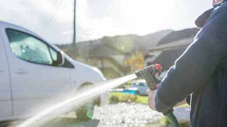 myjnia samochodowa : Kid spraying car with compressed water close up. Boy with water spray gun washing away dirty mud from white family car on a sunny day.