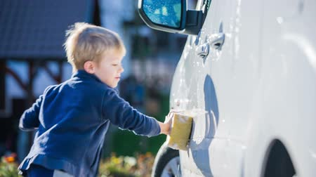 myjnia samochodowa : Kid washing car with yellow sponge. Medium shot of young boy helping washing family car with sponge and soap on a sunny day.
