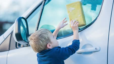 lavagem : Kid washing car windows close up. Child helping family clean big white car, kid having problem reaching higher than side windows. Vídeos