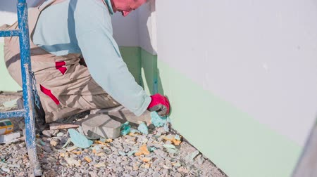 kielnia : Manson cutting away dried propylene from walls. Close up slow motion removing parts of dried propylene around blocks of polystyrene  on a house walls.