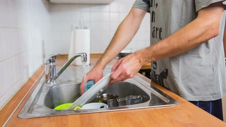 dish : Cleaning kitchenware under water in kitchen. Close up of male person cleaning plates and kitchenware with water from pipe and sponge.