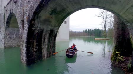 slovinsko : Rowing on boat under a bridge. Aerial shot of flying under a rock bridge while man rowing on wooden boat with swimming jacket on. Dostupné videozáznamy