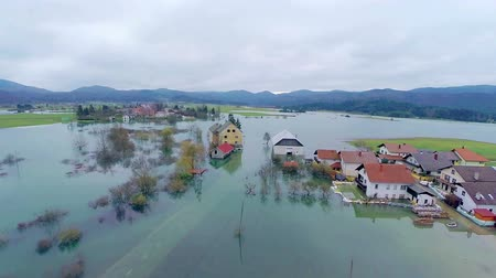 floods : Flooded houses in village water all around. Aerial shot of whole landscape with houses under water after massive rainfall in Slovenia. Stock Footage