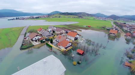 slovinsko : Flying around houses in flooded water. Aerial shot over homes after flooding disaster in countryside with houses in water.