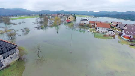 повреждение : Flying close to flooded water. Aerial shot of flooded area in countryside of Slovenia. Houses in water, farmland and objects flooded. Стоковые видеозаписи