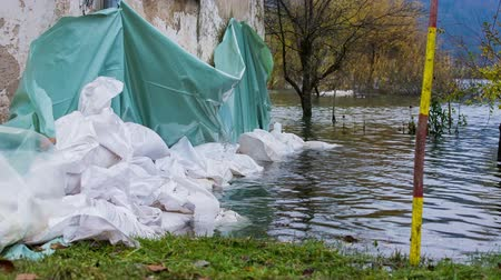 повреждение : Sand bags around the house walls saving from flood. Flooding disaster after massive rainfall, houses in danger of being flooded.