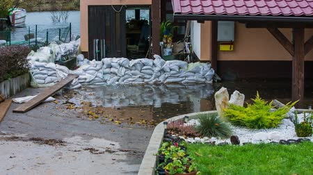 floods : Sandbag wall around house. Protecting home against flood with white sandbags, making a protective wall around.