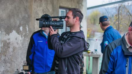 жить : PUDOB, SLOVENIA - OCTOBER 2014: Television news camera man holding big camera. Different news TV media with reporters and camera guys on terrain working.