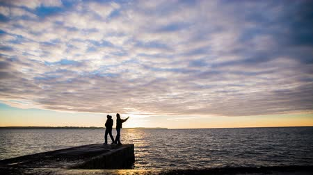 oceânico : Beautiful sunset and fisherman at sea.Two fisherman under hoodie with fishing rod catching fishes in sea at dawn wide lens with colorful clouds. Stock Footage