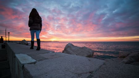 oceânico : Person walk on stone pier at sea with beautiful background.Wide jib shot of woman in warm clothes and boots walking on stone wall with beautiful sunset colors on sea surface and clouds.