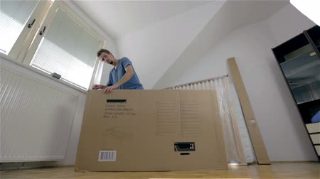 мебель : Person unpacking big box in apartment. Wide low angle shot of young attractive man in big room unpacking packages with furniture elements.