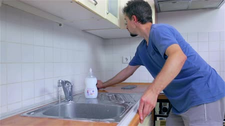 köpük : Man cleaning kitchen sink with sponge. Young attractive man in new home, checking and cleaning kitchen before using with own dishes.